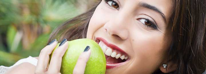 Wisdom Tooth Extractions Little Elm - A Smiling girl with an apple